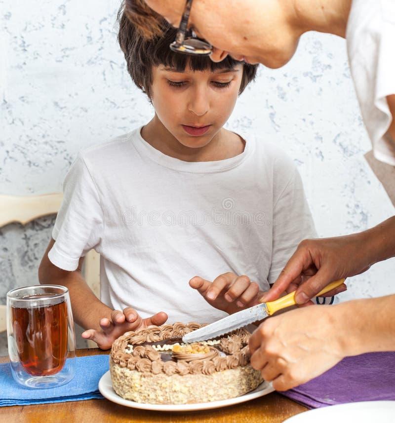 La mamma con il figlio ha tagliato una torta di compleanno immagini stock