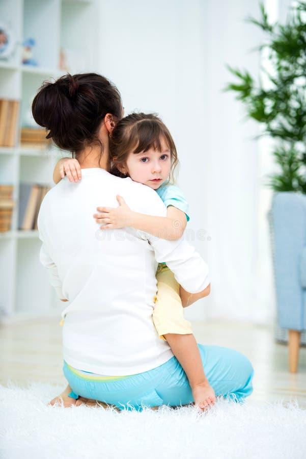 La mamma consola sua figlia gridante Non si preoccupi, non gridi fotografia stock
