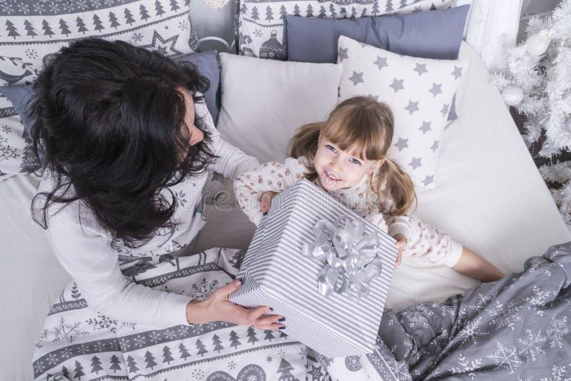 La mamma dà un regalo alla figlia fotografia stock libera da diritti