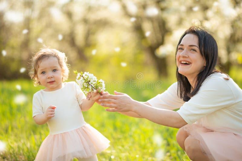 La mamma d? al suo bambino un ramo di fioritura in un parco di fioritura Umore di estate e di primavera fotografia stock libera da diritti