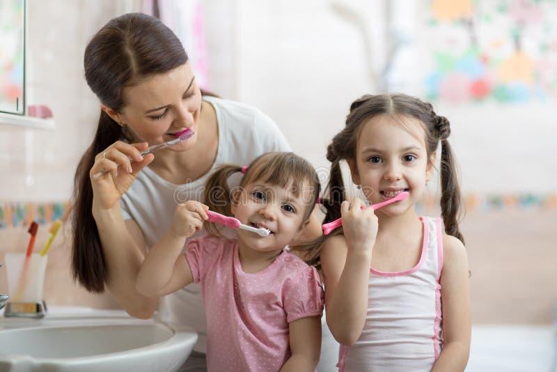 La mamma della famiglia e due bambine puliscono i loro denti fotografie stock