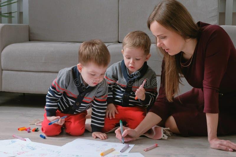La mamma della famiglia e due fratelli gemelli riuniscono gli indicatori ed hanno ritenuto le penne sedersi sul pavimento immagine stock libera da diritti