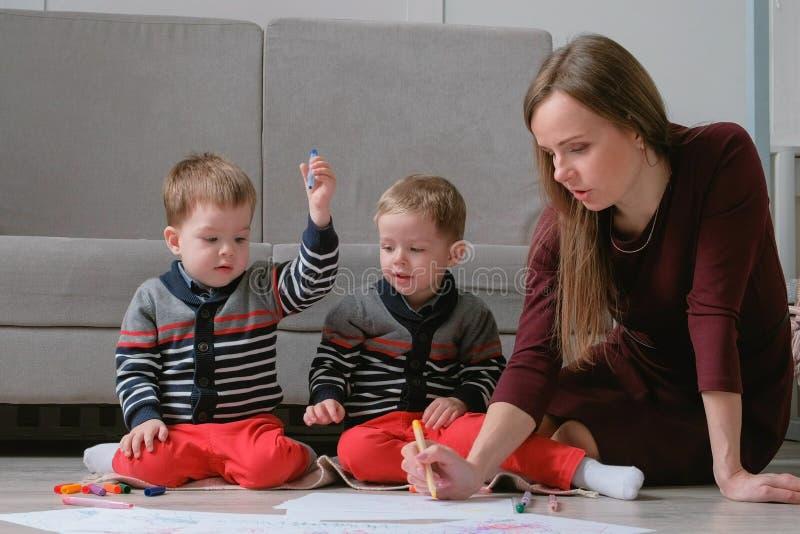 La mamma della famiglia e due fratelli gemelli riuniscono gli indicatori ed hanno ritenuto le penne sedersi sul pavimento fotografie stock libere da diritti