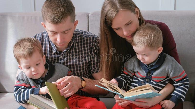 La mamma della famiglia, il papà e due fratelli gemelli hanno letto i libri che si siedono sul sofà Tempo della lettura della fam fotografia stock