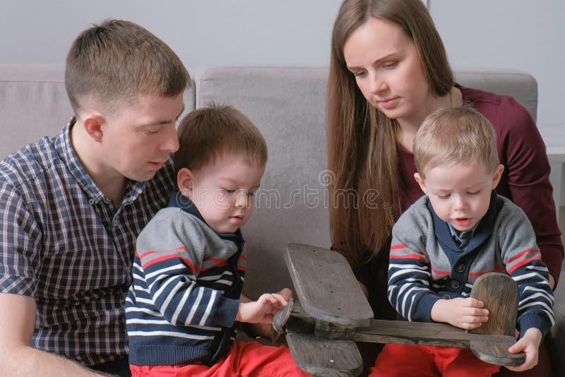 La mamma della famiglia, il papà e due fratelli gemelli hanno letto i libri che si siedono sul sofà Tempo della lettura della fam immagine stock libera da diritti