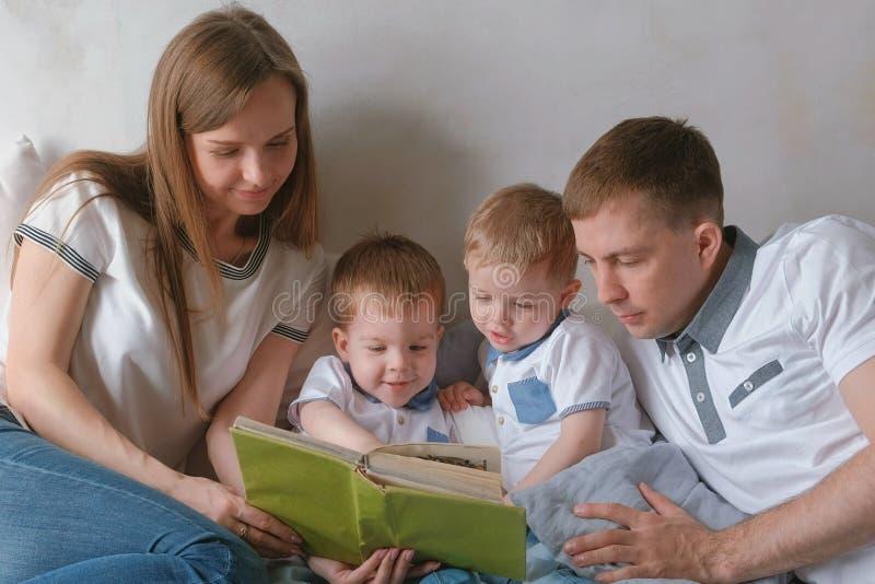 La mamma della famiglia, il papà e due fratelli gemelli hanno letto i libri mettere sul letto Tempo della lettura della famiglia fotografia stock