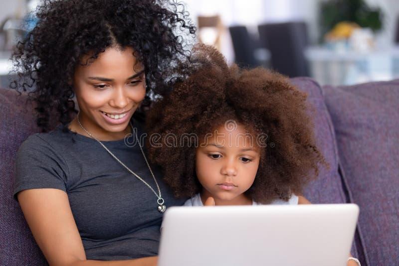 La mamma e la figlia afroamericana si rilassano usando il laptop insieme fotografie stock libere da diritti