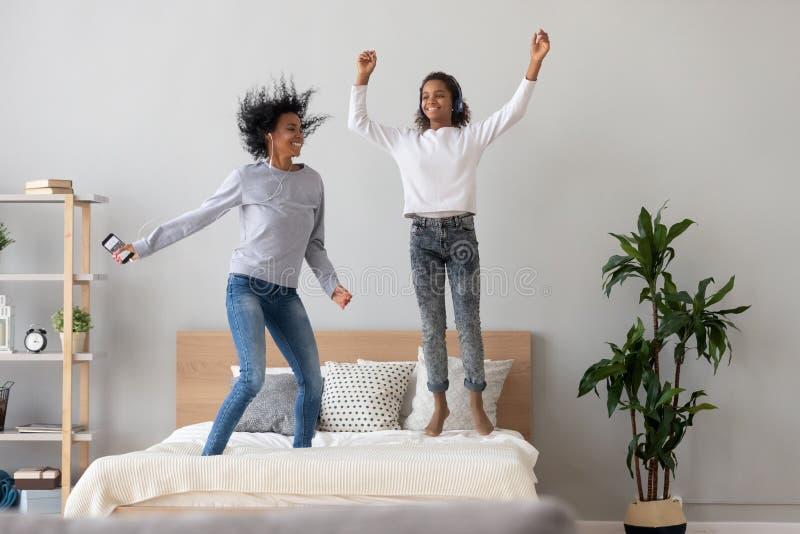 La mamma e la figlia nere felici saltano su musica d'ascolto del letto fotografia stock