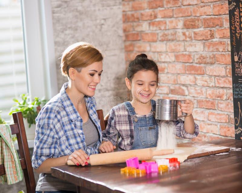 La mamma e la figlia preparano i biscotti nella cucina fotografia stock libera da diritti