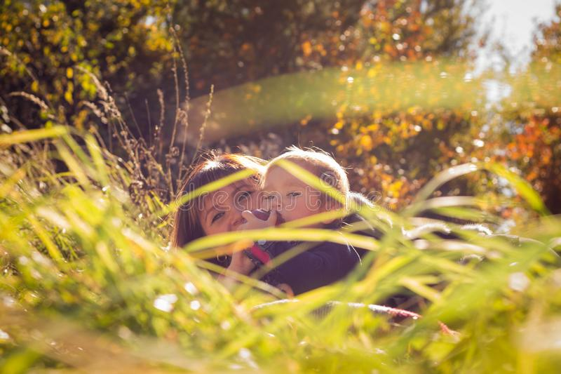 La mamma e la figlia si trovano nell'erba contro lo sfondo degli alberi di autunno immagini stock libere da diritti