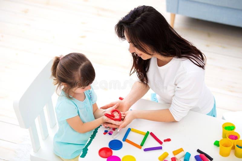 La mamma e la figlia sorridenti scolpiscono il cuore e la nuova casa di plasticine Creatività dei bambini Infanzia felice Sogni d immagini stock libere da diritti