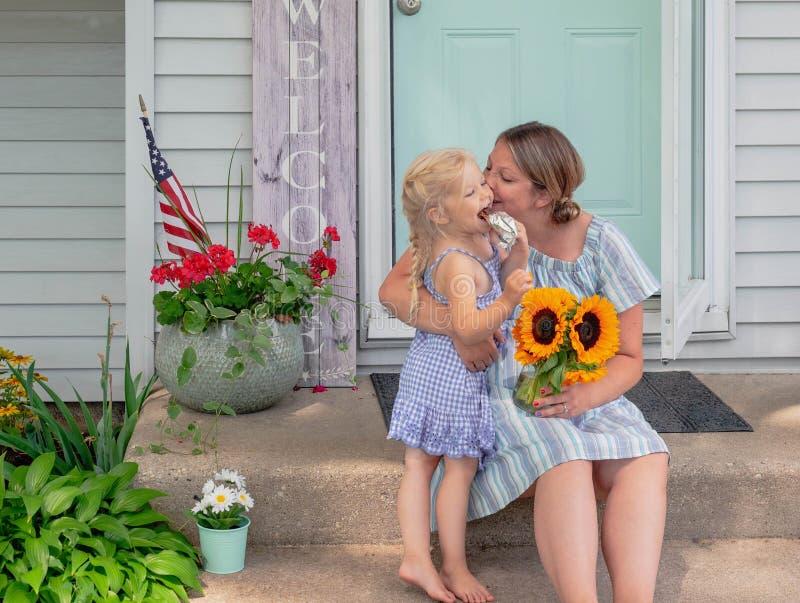 La mamma e la giovane figlia che si siedono sulla parte anteriore fa un passo a casa fotografie stock