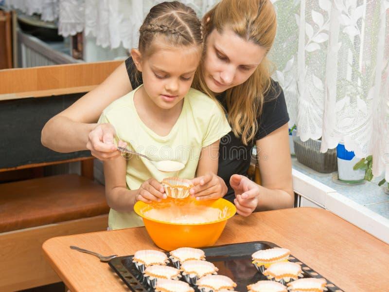 La mamma e la figlia sette anni colano la pastella nello stampo per i muffin bollenti fotografia stock