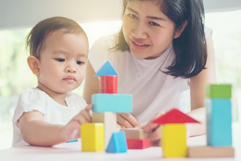La mamma e la ragazza asiatiche scherzano il gioco con i blocchi Effetti d'annata e fotografia stock