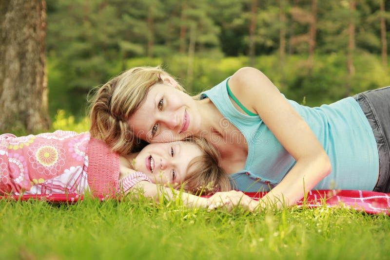 La mamma e la sua piccola figlia si trovano sull'erba immagini stock libere da diritti