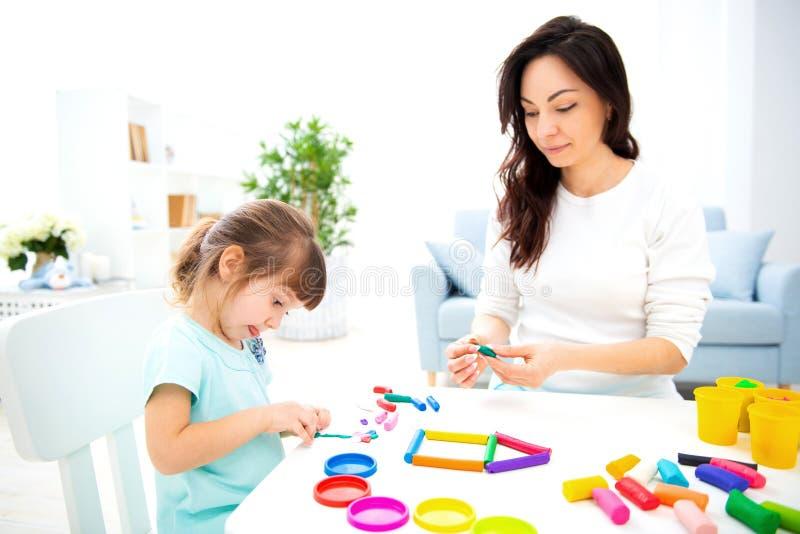 La mamma e la piccola figlia scolpiscono la nuova casa di plasticine Sviluppo infantile e istruzione Svago della famiglia con un  fotografia stock libera da diritti