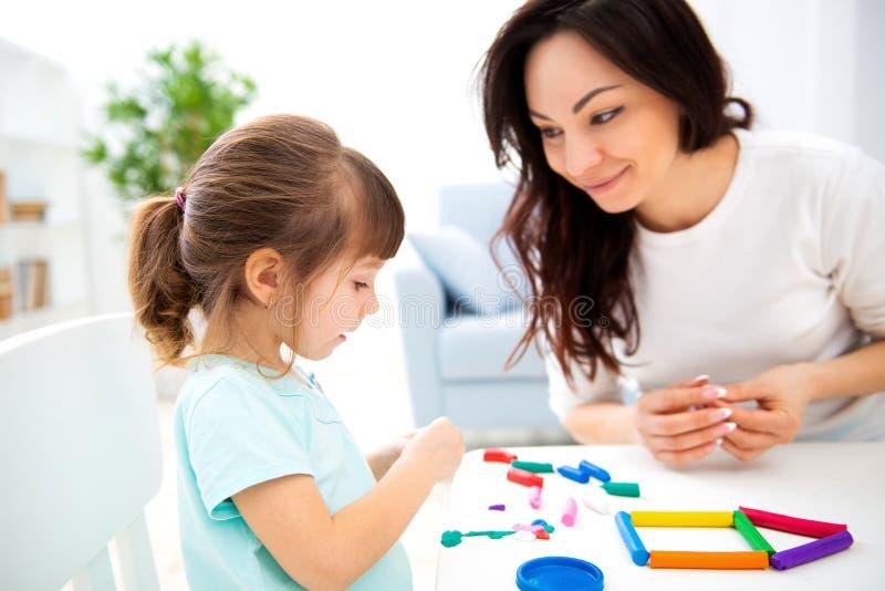 La mamma e la piccola figlia scolpiscono la nuova casa di plasticine Sviluppo infantile e istruzione Svago della famiglia con un  immagini stock libere da diritti