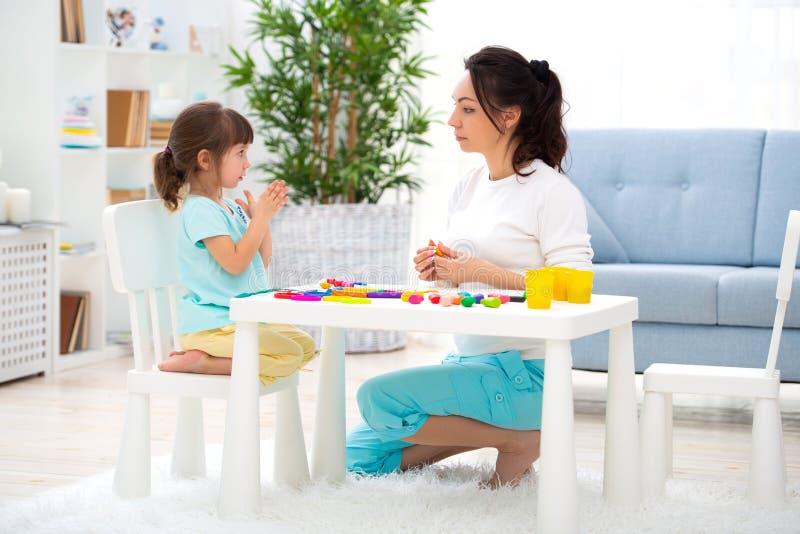 La mamma e la piccola figlia scolpiscono la nuova casa di plasticine Sviluppo infantile e istruzione Svago della famiglia con un  fotografia stock