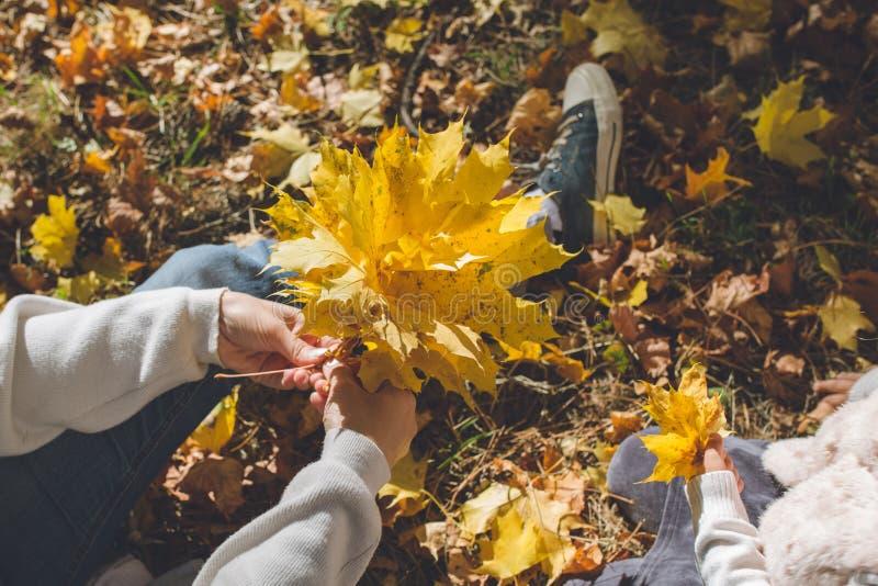 La mamma e poca figlia stanno sedendo in un prato nella foresta di autunno e stanno tessendo una corona delle foglie gialle immagine stock
