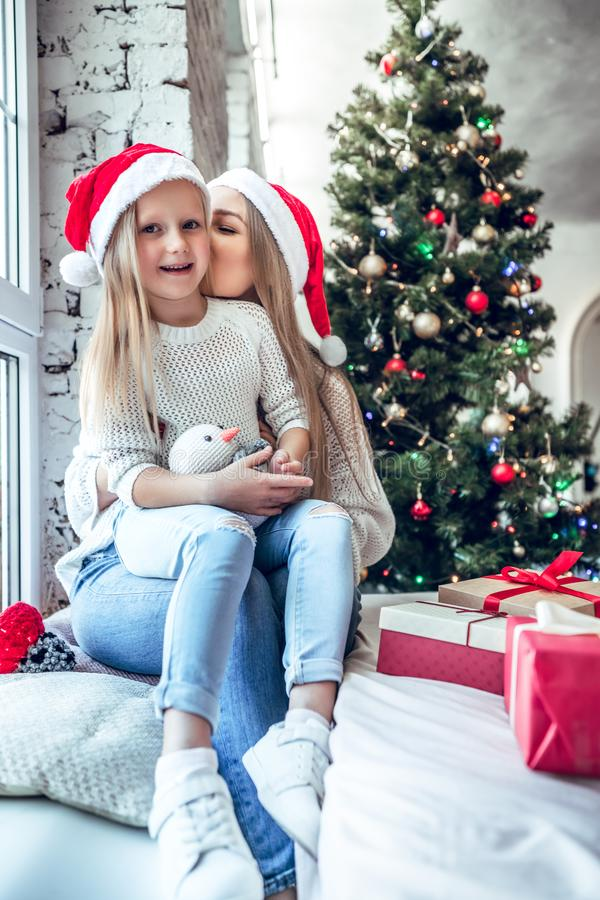 La mamma e la sua piccola figlia in Santa Hat stanno spendendo insieme il tempo vicino all'albero di natale a casa fotografia stock libera da diritti