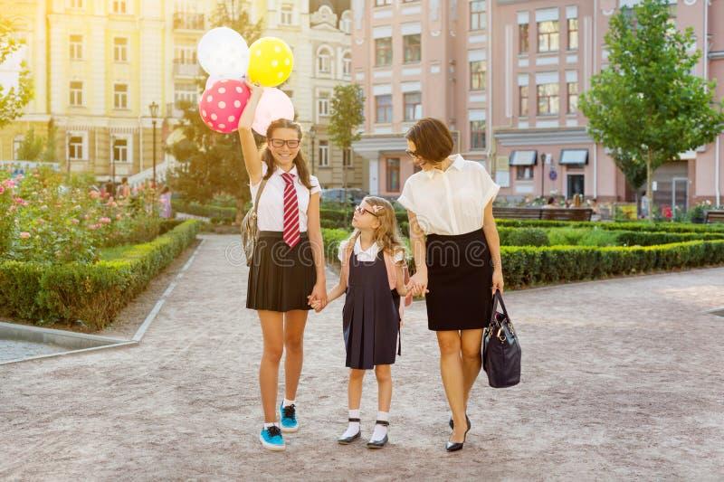 La mamma ed i bambini che si tengono per mano, vanno a scuola fotografie stock libere da diritti