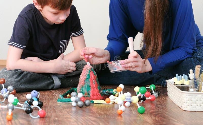 La mamma ed il figlio fanno l'esperienza con il vulcano del plasticine a casa Reazione chimica con emanazione di gas immagine stock