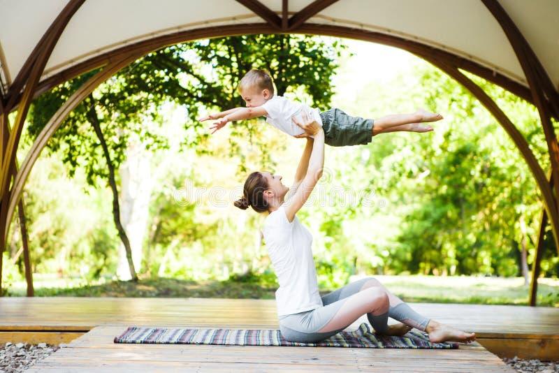 La mamma ed il figlio stanno praticando l'yoga nel parco immagine stock libera da diritti