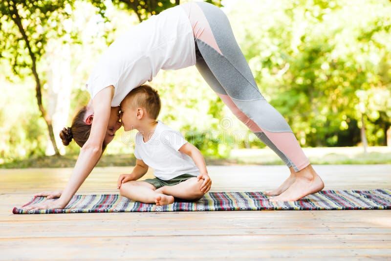 La mamma ed il figlio stanno praticando l'yoga nel parco immagine stock