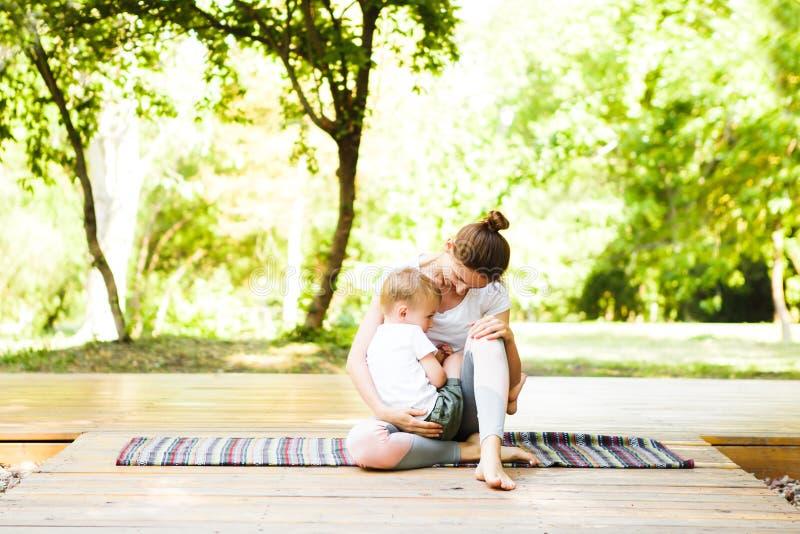 La mamma ed il figlio stanno praticando l'yoga nel parco fotografia stock