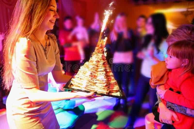 La mamma felice si congratula il bambino con la torta di compleanno e presenta il gi immagine stock libera da diritti