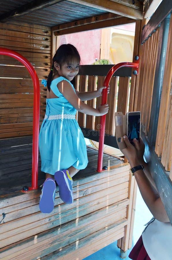 La mamma fotografa sua figlia con il suo smartphone quando ad un campo da giuoco pubblico immagine stock libera da diritti