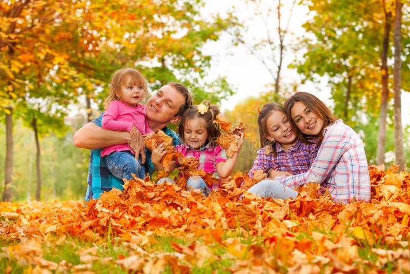 La mamma, il papà e le figlie giocano nel mucchio delle foglie di acero fotografia stock