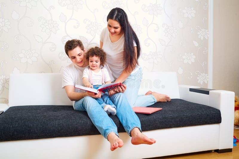 La mamma, il papà ed il bambino hanno letto un libro sullo strato nella stanza genitori fotografia stock libera da diritti