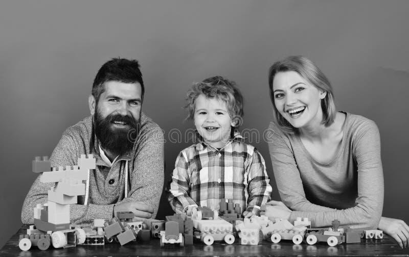 La mamma, il papà ed il ragazzo su fondo rosso costruiscono le automobili dai blocchi di plastica La giovane famiglia passa il te immagini stock