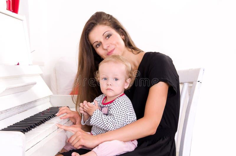 La mamma insegna alla figlia a giocare il piano immagine stock libera da diritti