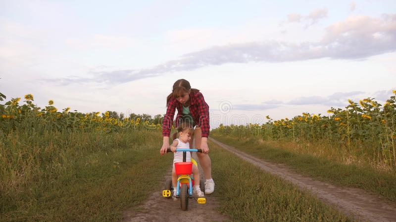 La mamma insegna alla figlia a guidare una bici su una strada campestre in un campo dei girasoli un piccolo bambino impara guidar fotografia stock