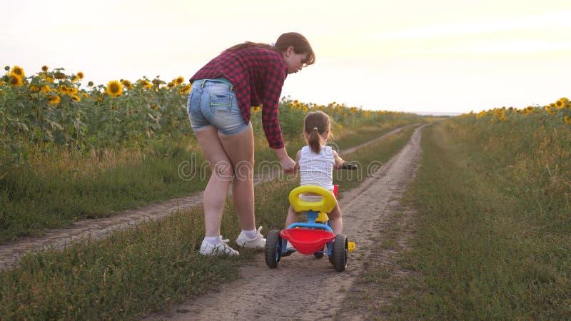 La mamma insegna alla figlia a guidare una bici su una strada campestre in un campo dei girasoli un piccolo bambino impara guidar immagini stock