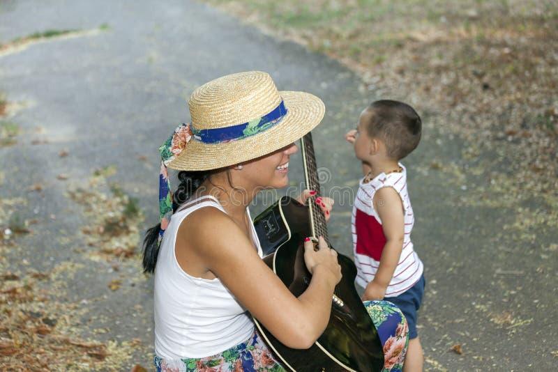 La mamma intrattiene suo figlio mentre gioca la chitarra immagini stock libere da diritti