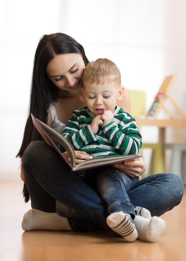 La mamma legge con un bambino immagine stock