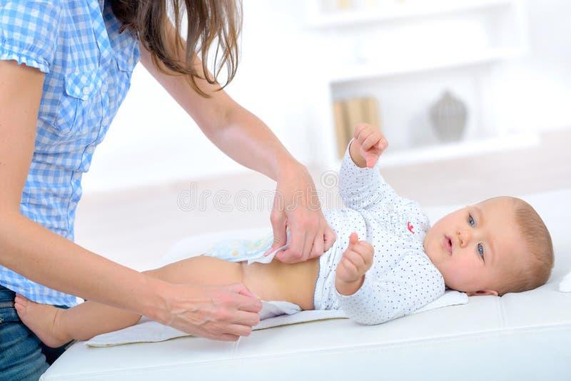 La mamma mette sopra la tavola cambiante del bambino del pannolino fotografia stock