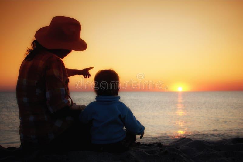 La mamma mostra il suo giovane tramonto del figlio al mare fotografia stock