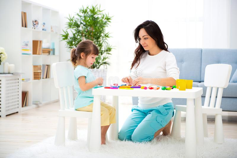 La mamma positiva sorridente e poca figlia scolpiscono di plasticine Sviluppo infantile e istruzione Svago della famiglia con un  immagine stock