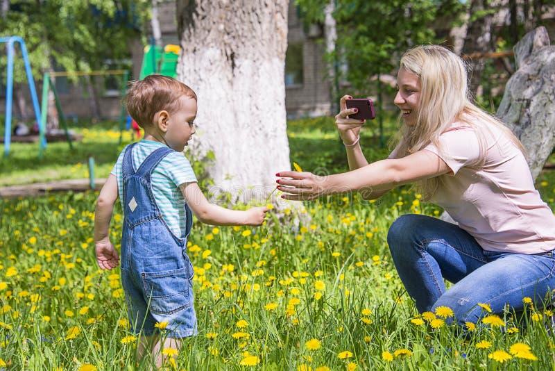 La mamma prende le immagini del bambino nel parco immagini stock libere da diritti