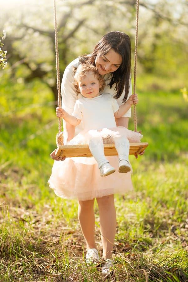 La mamma rotola il bambino su un'oscillazione nei giardini o nel parco di fioritura Festa della Mamma, l'8 marzo, umore della mol fotografia stock libera da diritti