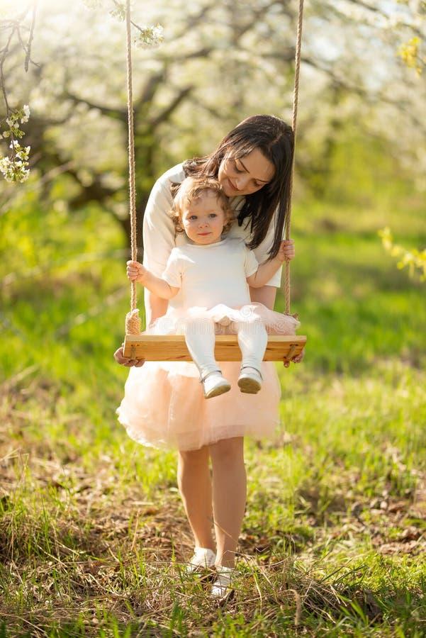 La mamma rotola il bambino su un'oscillazione nei giardini o nel parco di fioritura Festa della Mamma, l'8 marzo, umore della mol fotografia stock