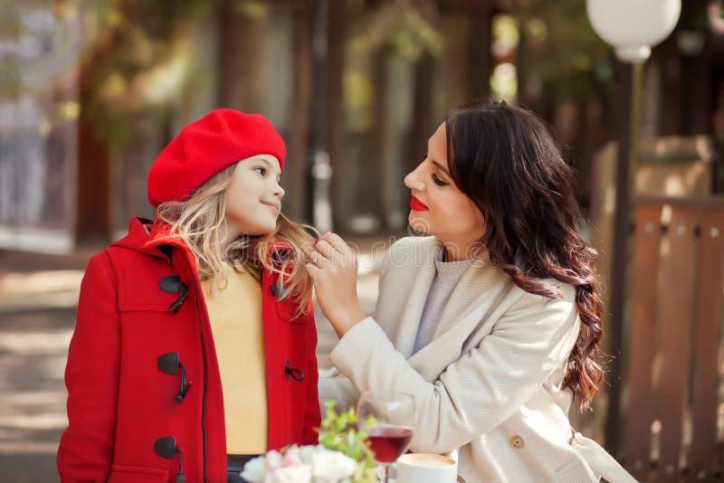 La mamma sorridente aiuta la piccola figlia carina a legarsi il cappotto rosso immagini stock