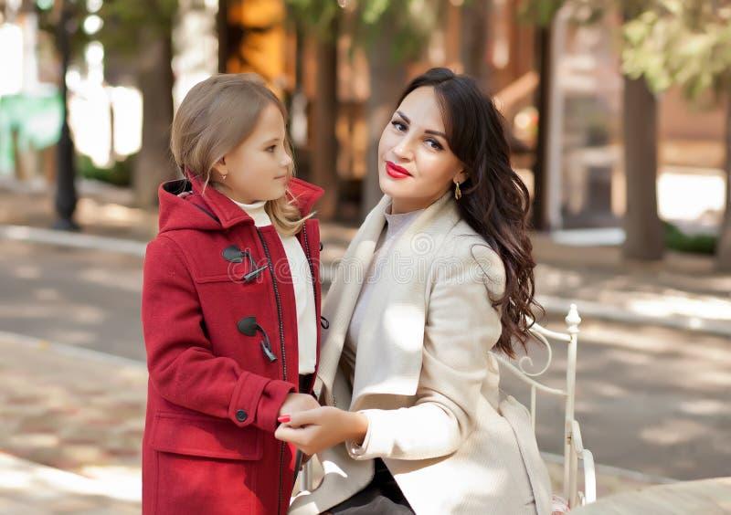 La mamma sorridente aiuta la piccola figlia carina a legarsi il cappotto rosso fotografie stock libere da diritti