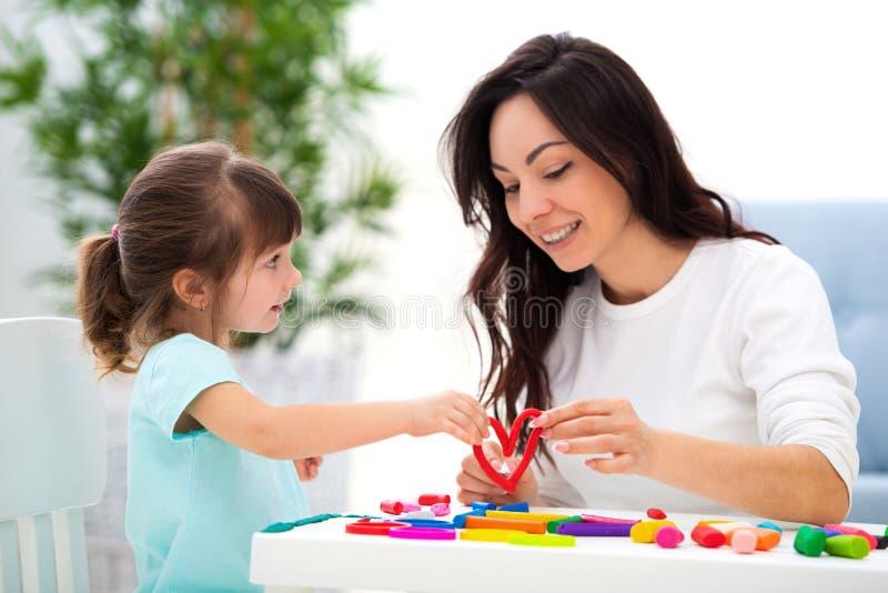 La mamma sorridente e poca figlia scolpiscono il cuore rosso di plasticine Sviluppo infantile e creatività Amore della famiglia,  fotografia stock