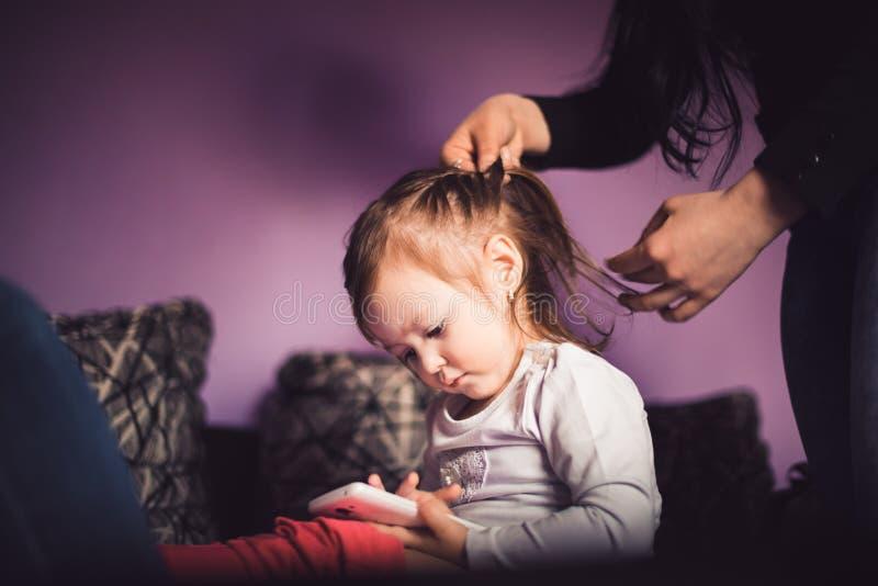 La mamma sta facendo l'acconciatura alla figlia immagine stock libera da diritti