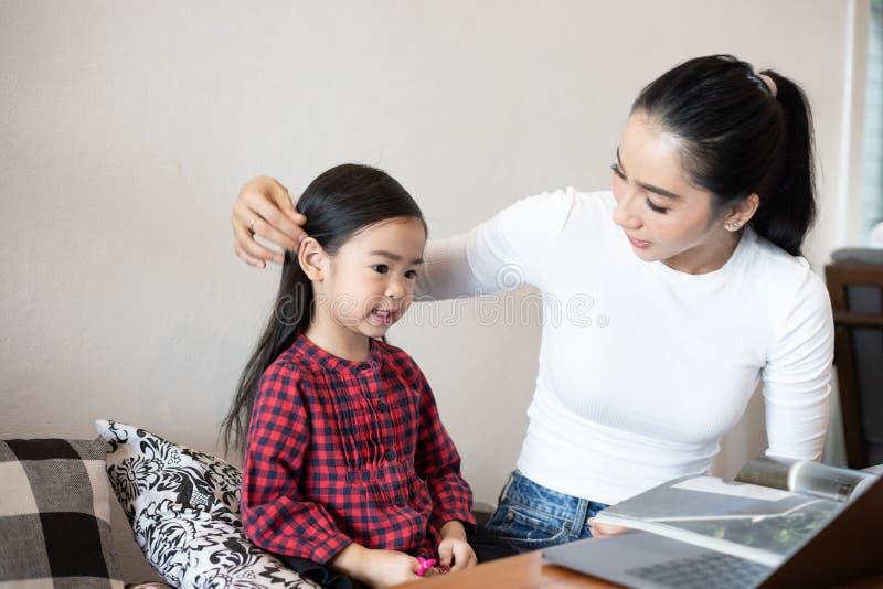 La mamma sta insegnando a sua figlia a leggere un libro e sta giocando il taccuino fotografia stock libera da diritti